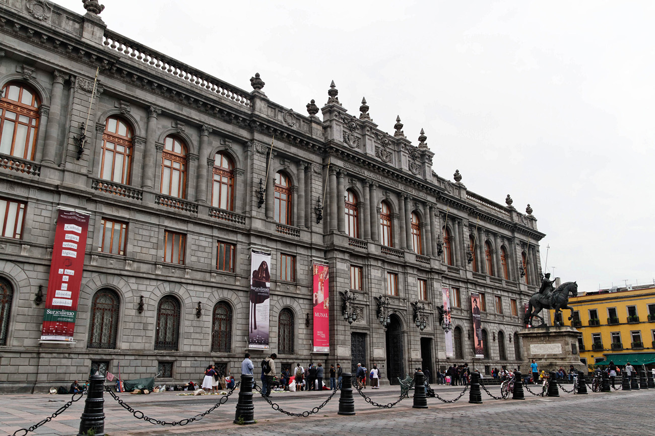 Large grey building in a city square in Mexico City.