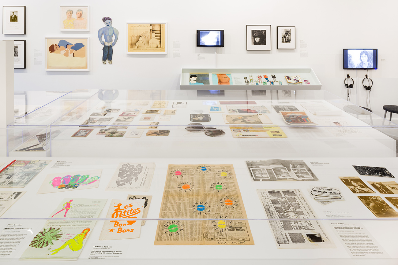 A gallery containing tables and display cases that include newspaper, prints, zines, photographs and other ephemera.