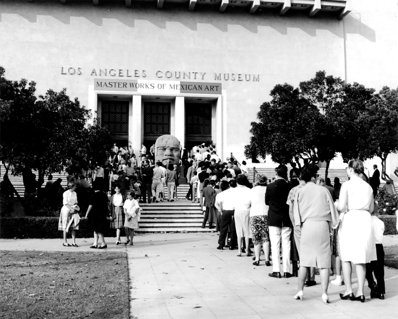 An older photo of many people lined up to visit the Los Angeles County Museum's exhibition titled Masterworks of Mexican Art. The line goes up a small staircase and there is a large stone Olmec head on top of the stairs.