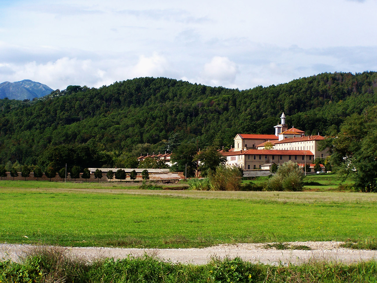 A photograph of a green luscious landscape. In the right third tucked along a hillside is a monastery with a red-tiled roof.