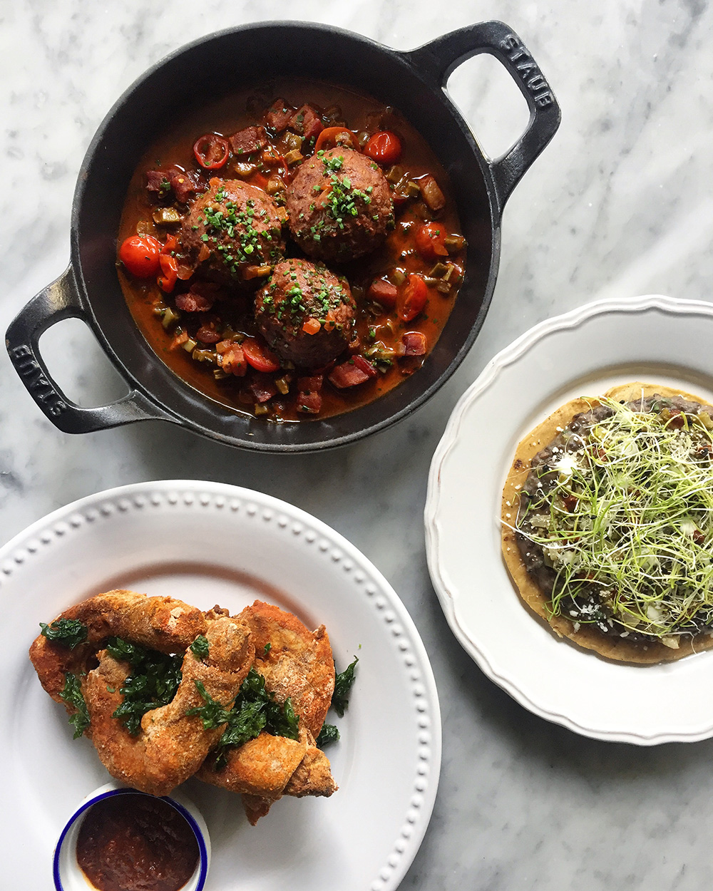 Bird's-eye view of three Latin American dishes, including meatballs in red sauce
