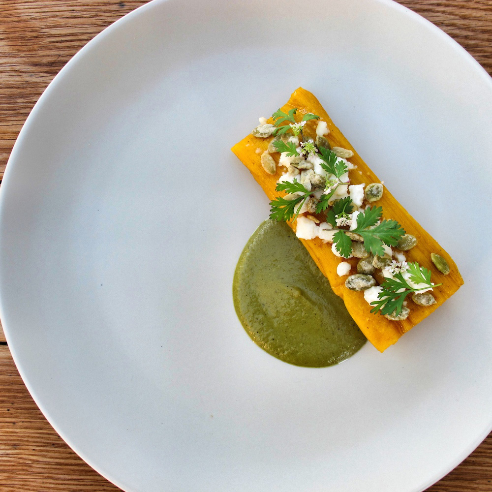 Bird's eye view of a plate with a tamale covered in crema, pepitas, and cilantro