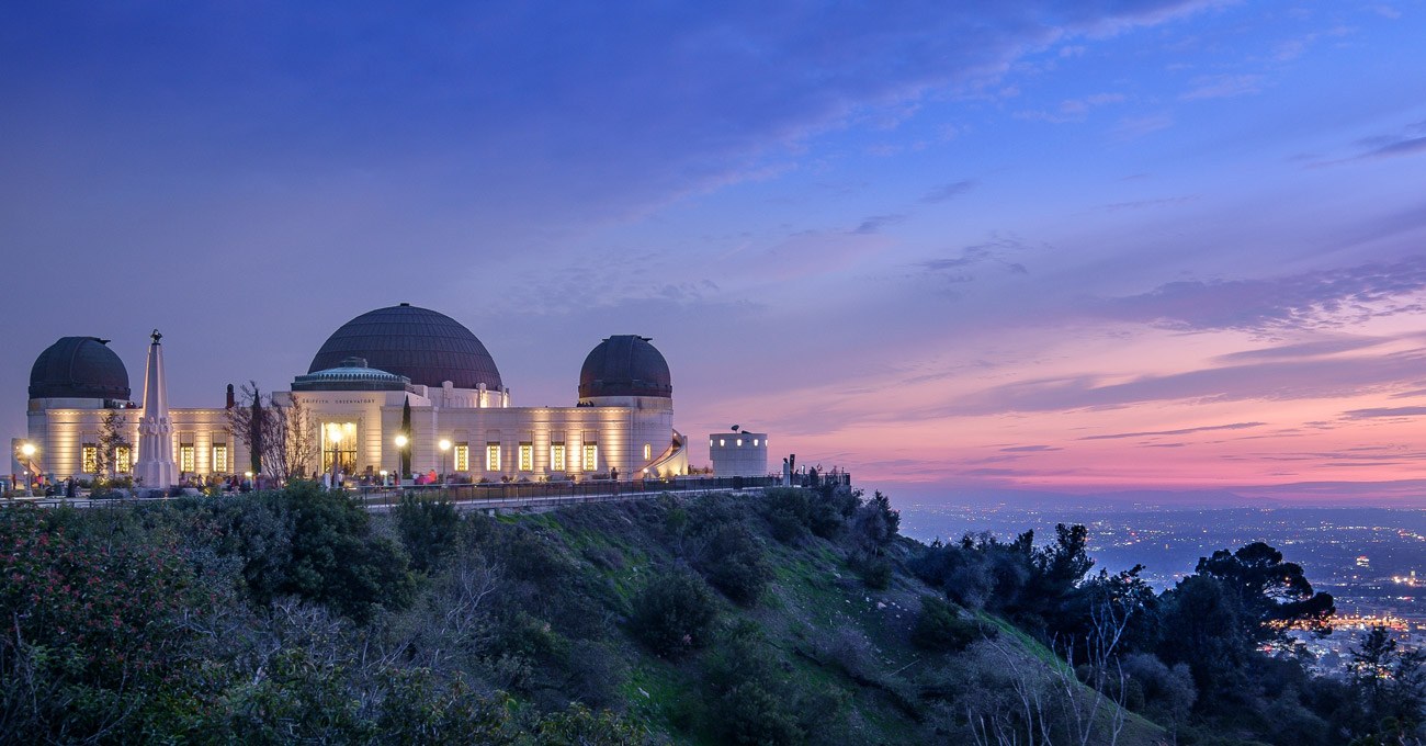 The domed roofs and white art deco facade of the Griffith Observatory lit at dusk with a sunset and the Los Angeles skyline.