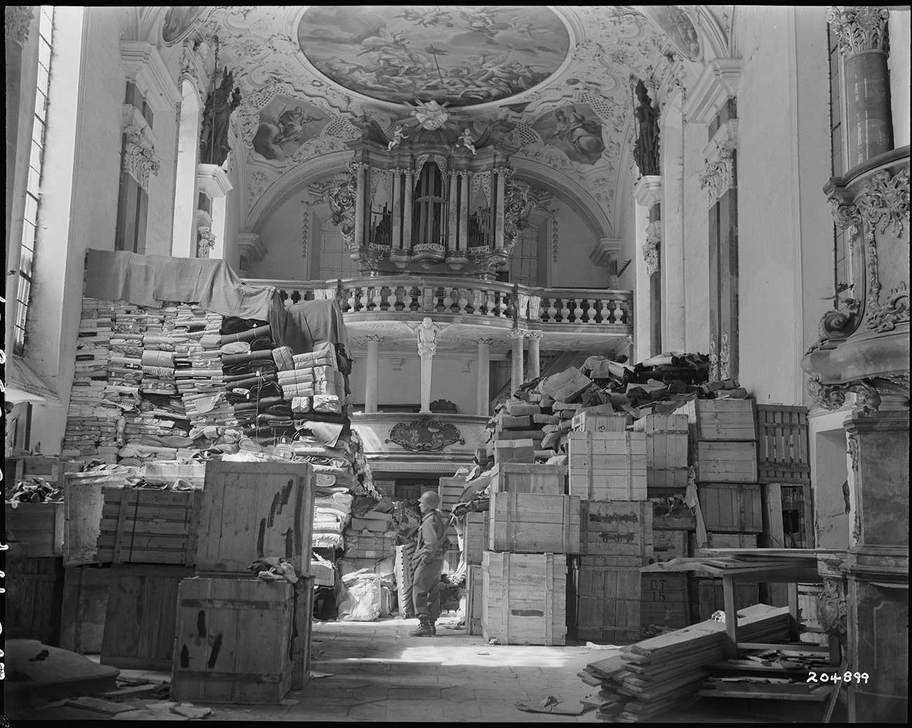 Black and white photograph of a Baroque church interior piled high with wooden crates of stolen art