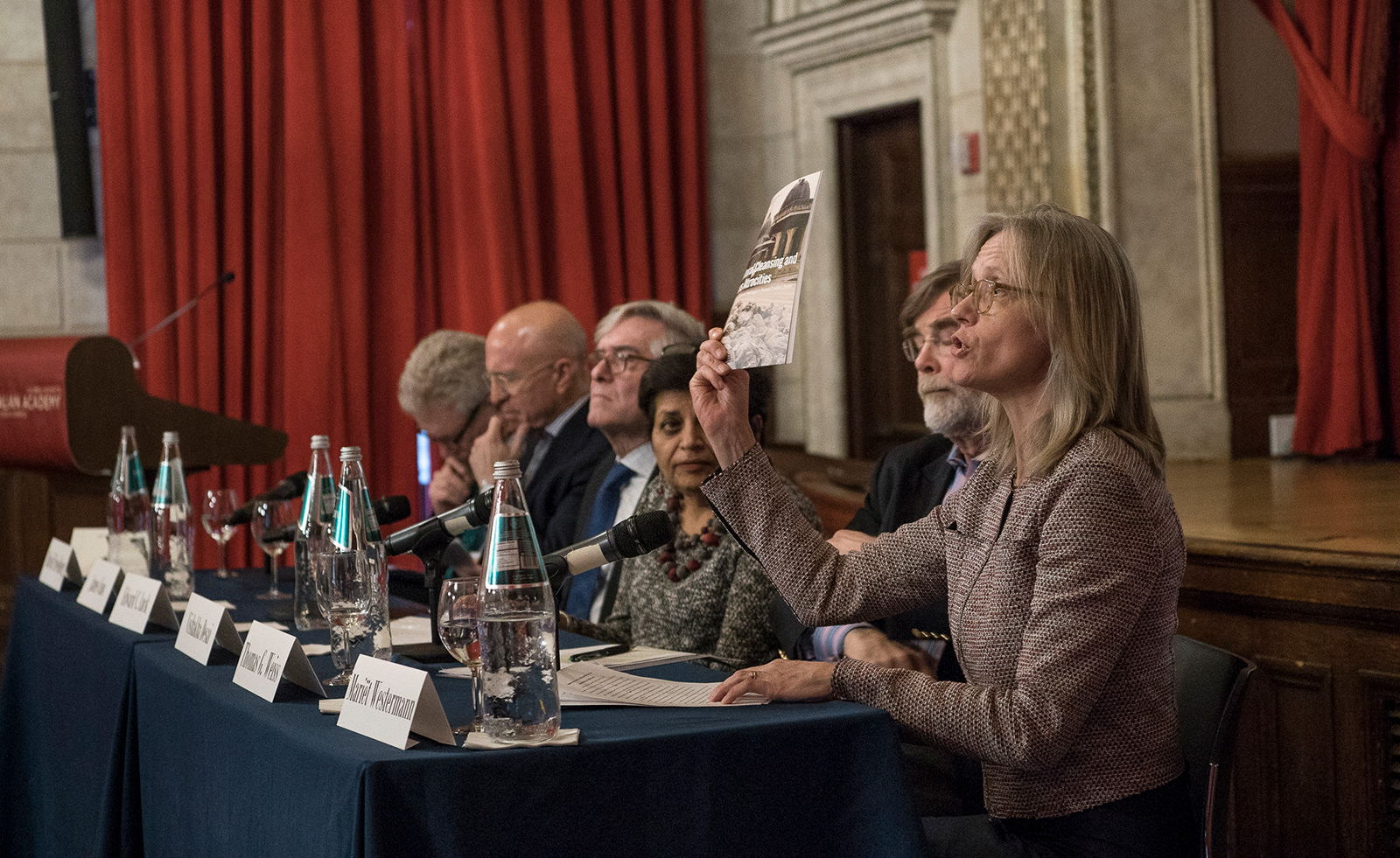 A speaker at a panel discussion makes a point about the need to protect cultural heritage, holding aloft a report on the subject
