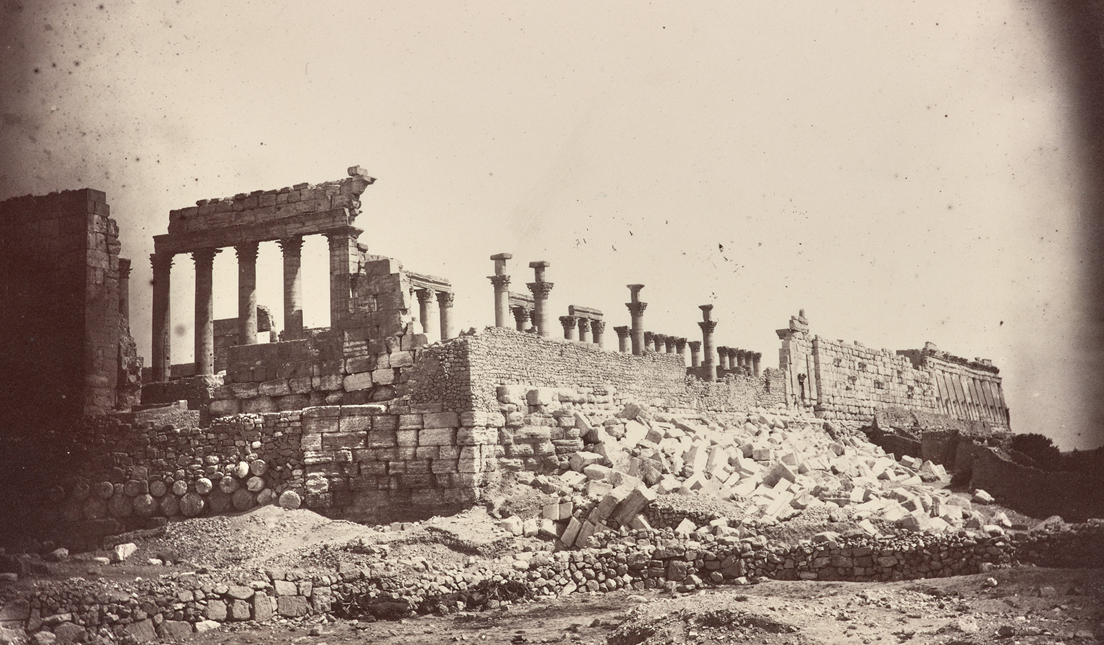 A sepia-toned photo showing a monumental set of ruins with Roman-style columns
