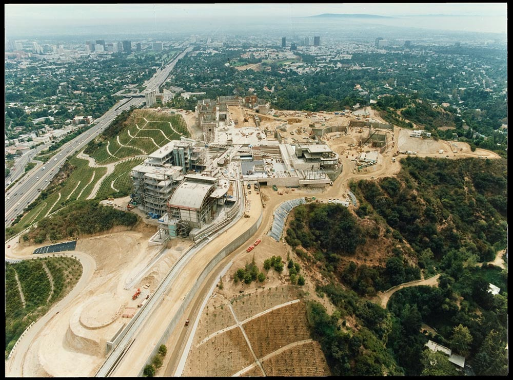 Aerial view of Getty Center site under construction from September 1994 surrounded by freeway and mountains