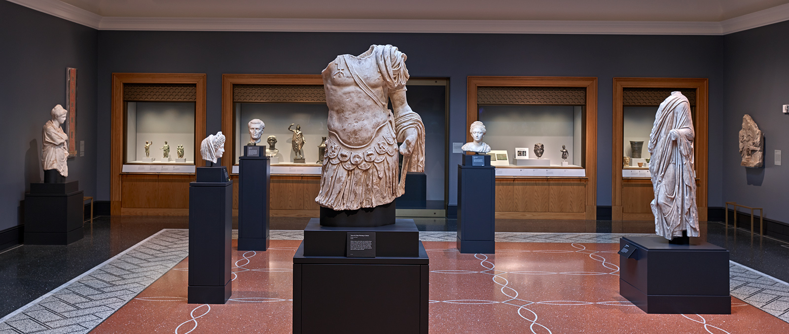 A wide-angle view of a gallery of ancient Roman sculpture with individual marbles on plinths