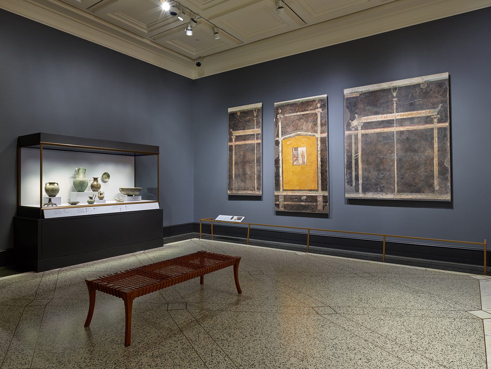 An empty gallery with blue walls contains a glass case of metal luxury goods at left and three large segments of an ancient Roman fresco at right