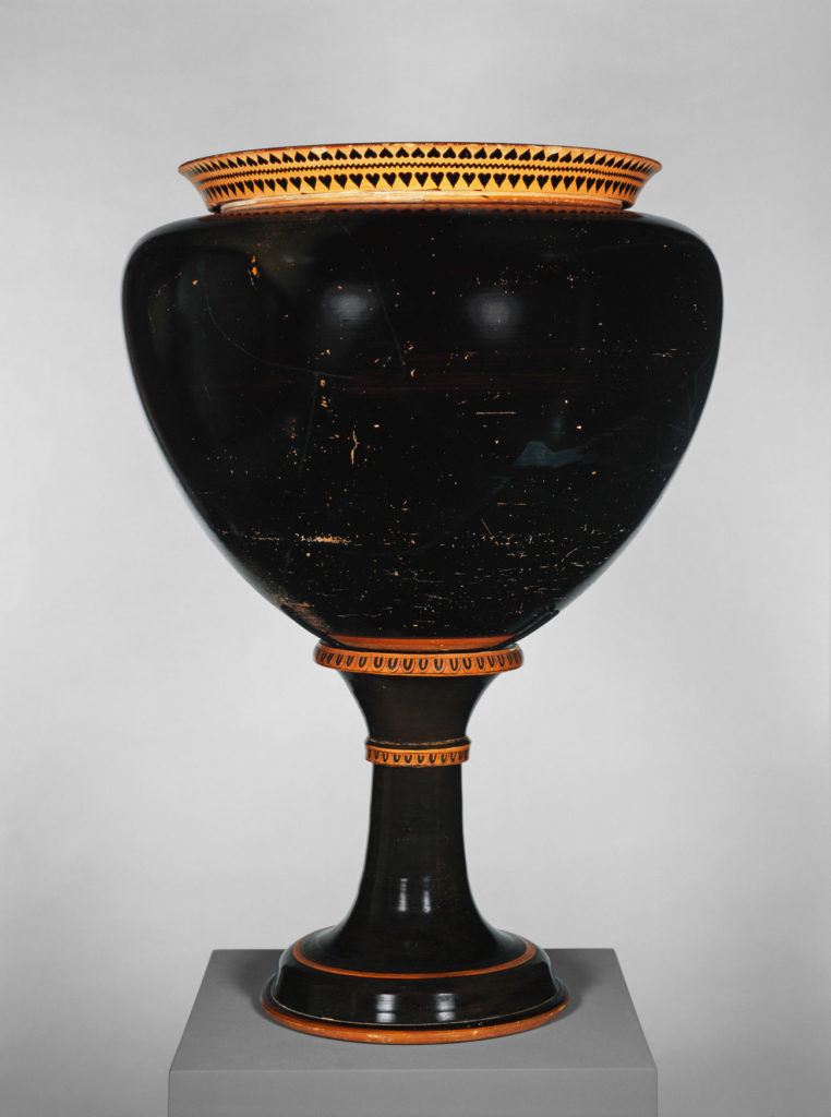 A black vessel with gold colored trim painted with heart and leaf patterns.