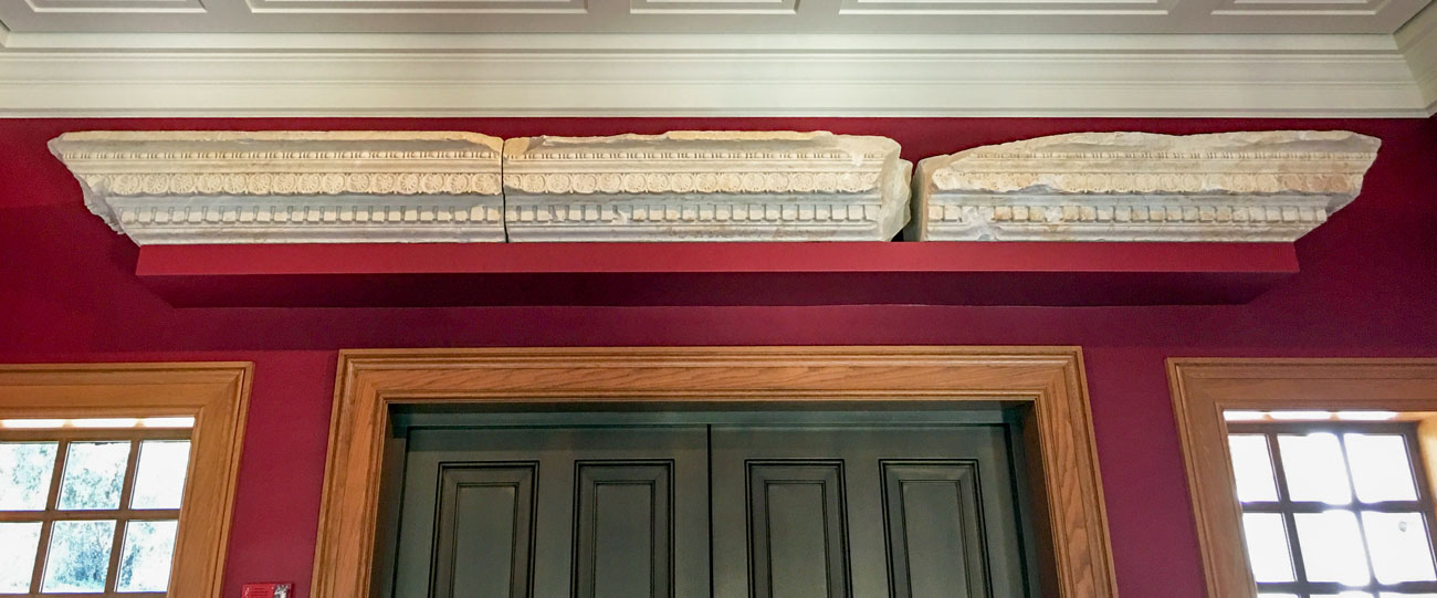 A carved marble cornice in three pieces mounted above a doorway