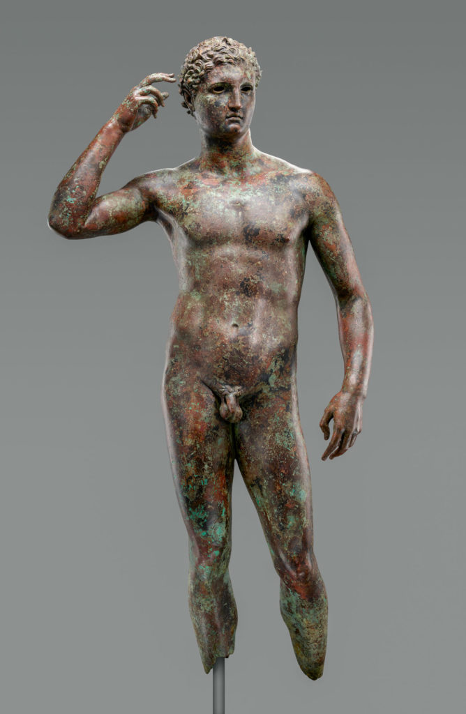 Bronze statue of a nude young man raising his right hand to his head. The lower legs are missing.