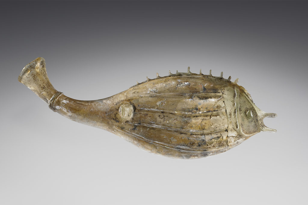 A pale green glass flask shaped like a fish, pictured from the side. It has small spines running along its back, four ridges along its side, and an open mouth.