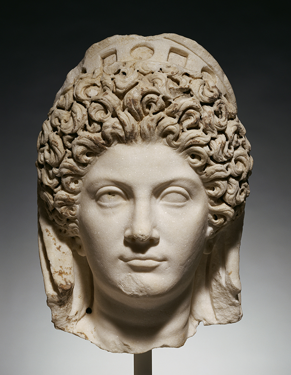 A marble head depicts a European woman with elaborate curls surrounding her face and wearing a crown.