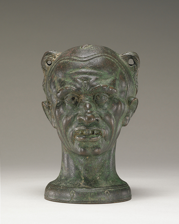 This greenish brown oil jar depicts a European man's head wearing a tight-fitting cap, his face bumpy and some teeth missing from his slightly open mouth. At the top left and right of his head are holes through which to pass a rope or chain.