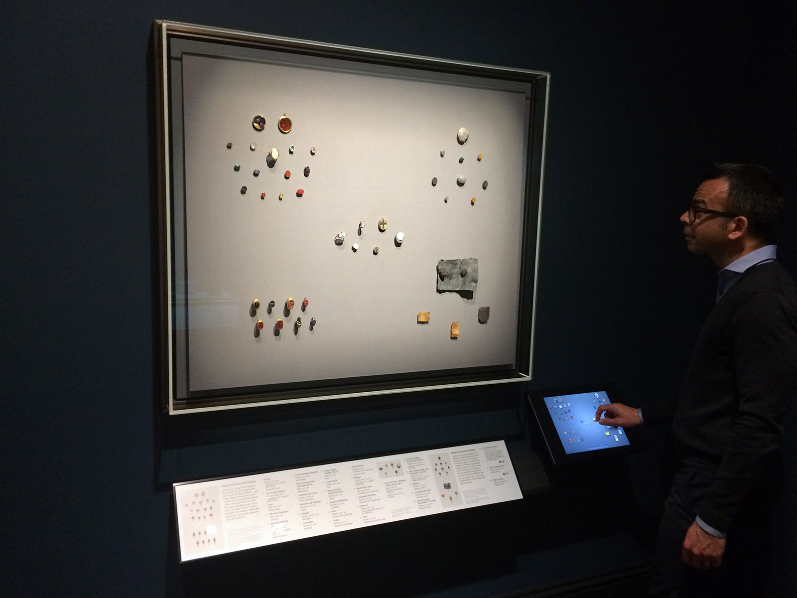 A dramatically lit showcase of gems and small metal treasures hands on a wall. To the right, a man uses an iPad that allows visual zooming