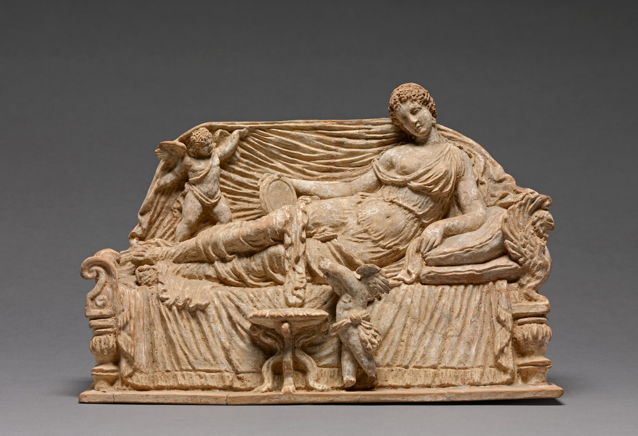 A finely detailed sculpture of a women holding a disc on a couch with two cherubs.