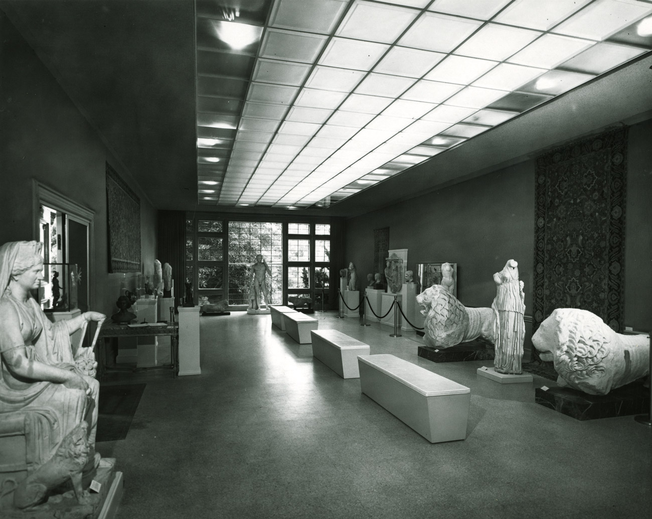 Black and white photo of a hall with Roman marble sculptures, tapestries on the walls and benches.