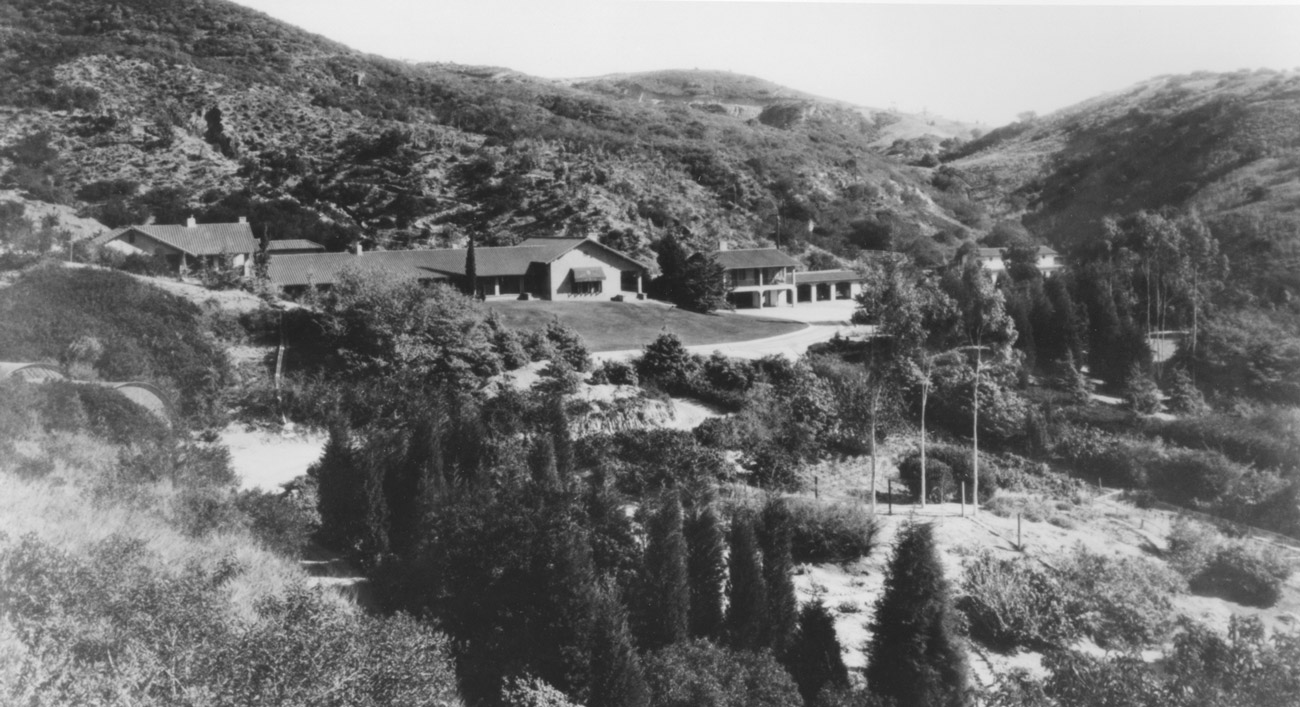Black and white photo of a house nestled in natural undeveloped hills with brush and trees.