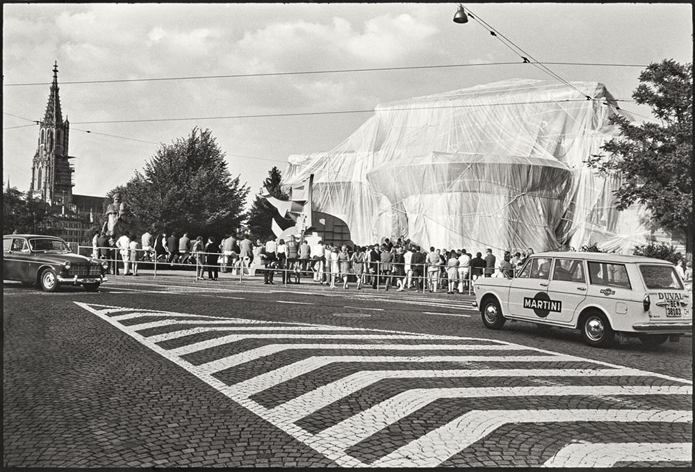 Black-and-white photograph of a building entirely wrapped in fabric with a crowd of people outside.