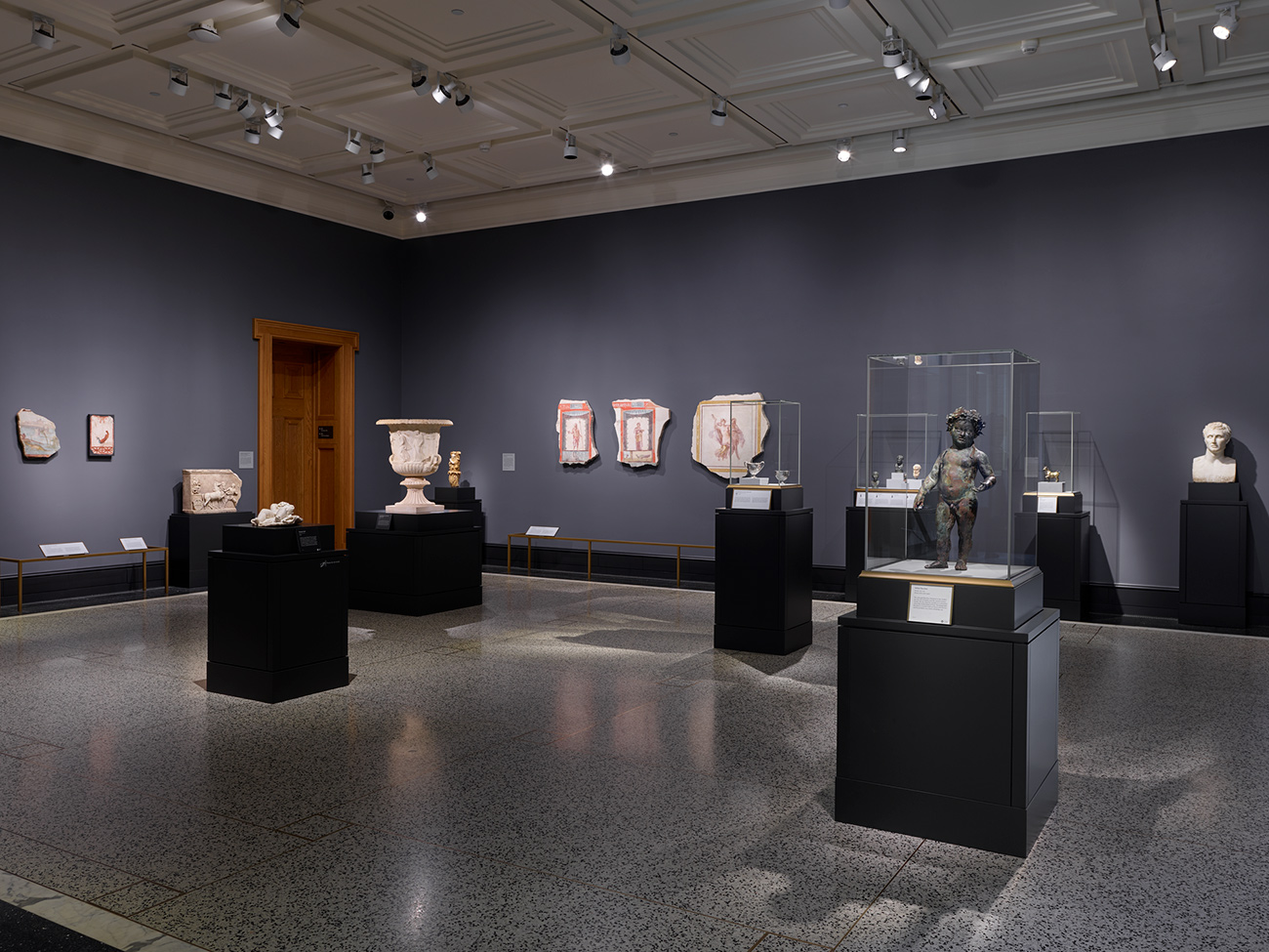 Wide-angle view of a gallery of small sculptures, vessels, busts, and fresco fragments