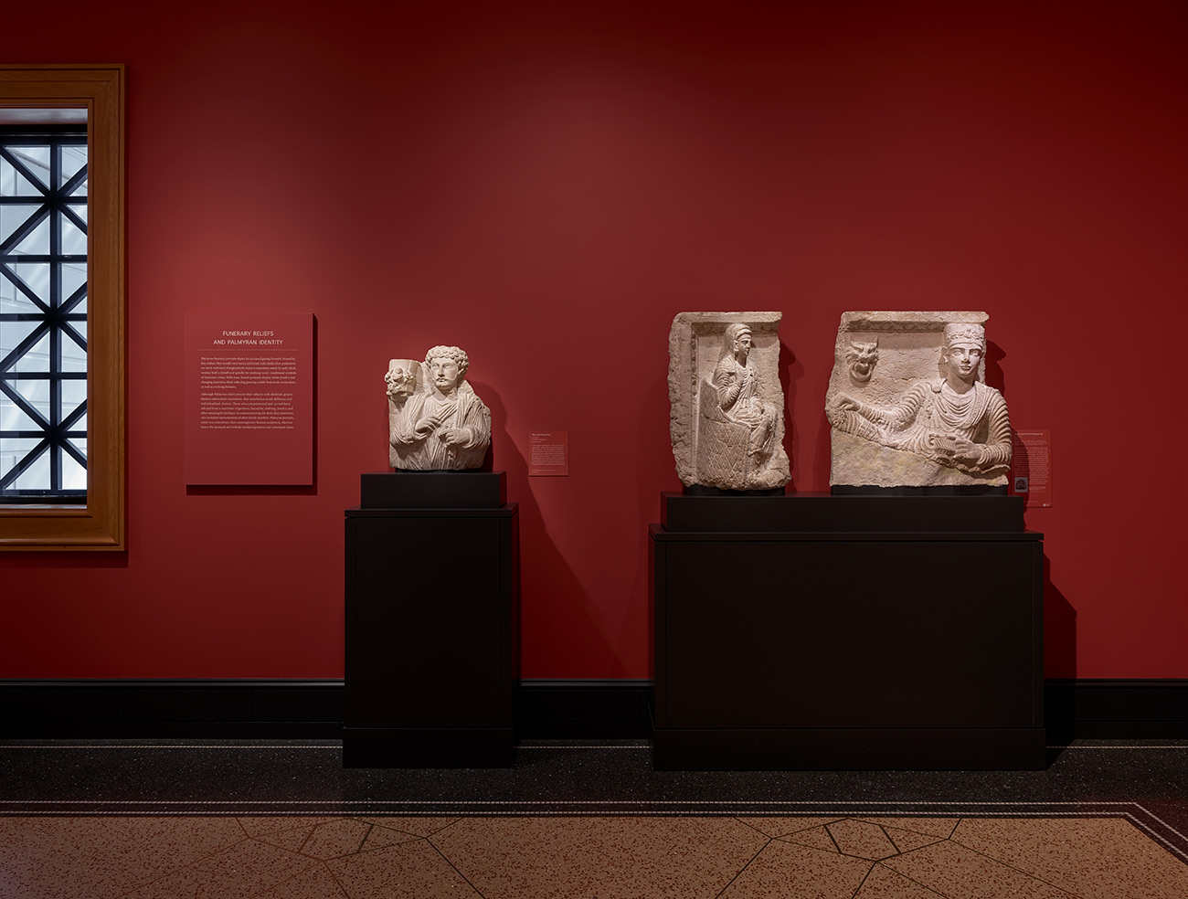 Three antique limestone sculptures sit on plinths, spotlit against a vibrant red wall