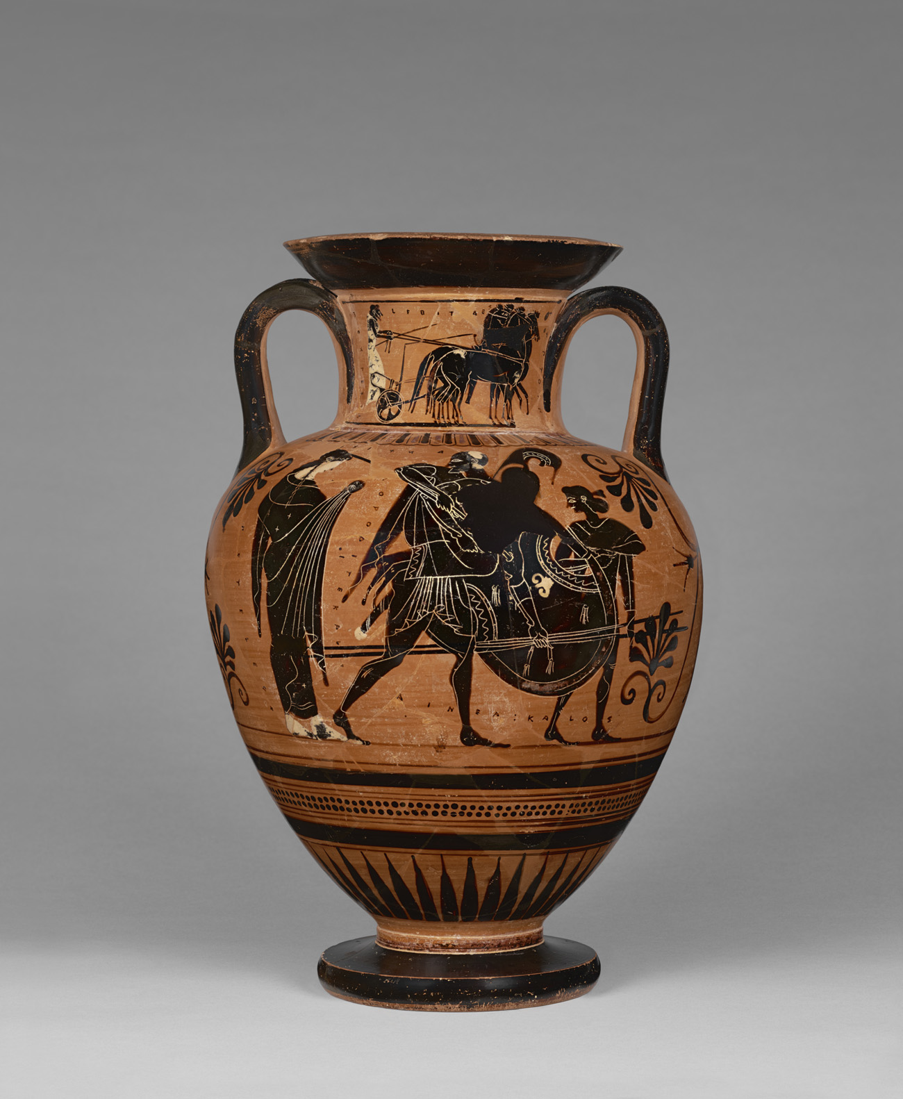 A large terracotta and black storage vessel with two small handles shows figures from Greek myth painted in black