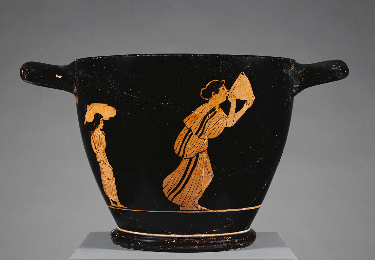 On a black bowl, a young woman is depicted stumbling forward as she drinks out of a large drink cup