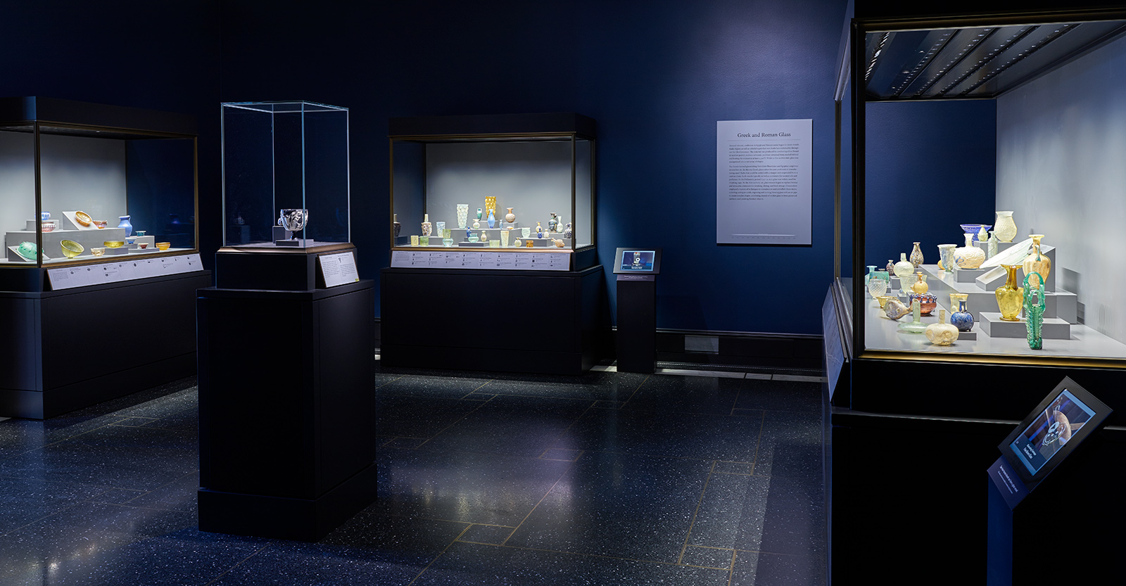 Interior view of a darkly lit gallery with showcases filled with small, vividly colored glass vessels