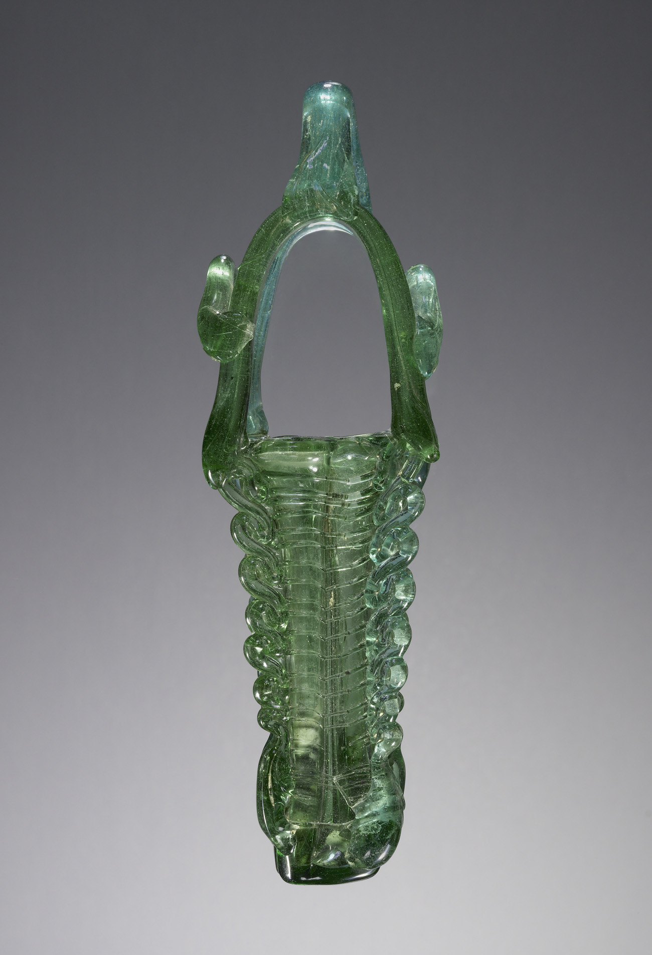 A thin, tall, intricately formed grass-green glass storage vessel with an elaborate looped top handle