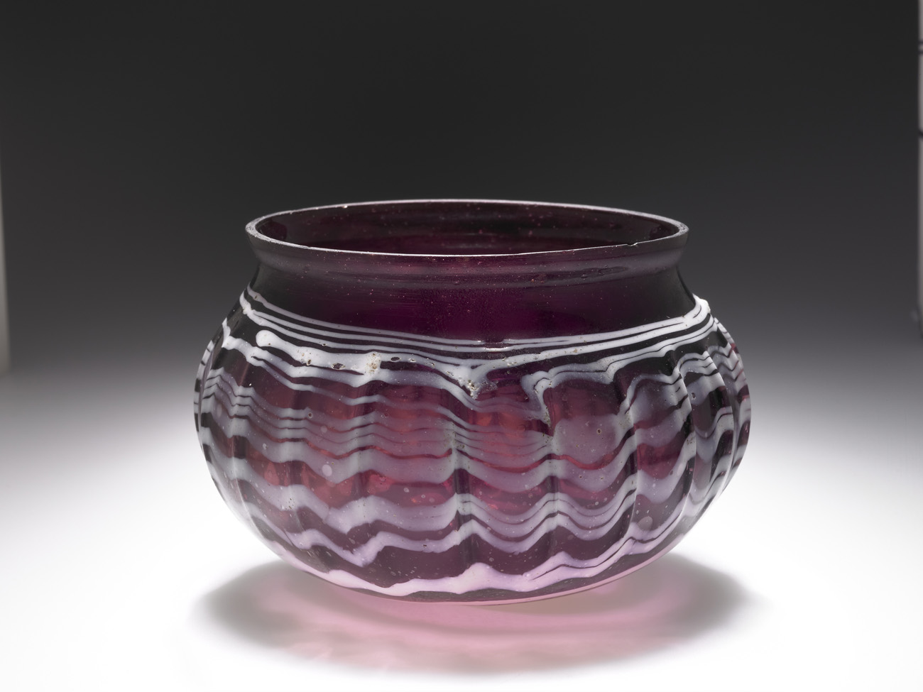 A squat, reddish purple glass bowl with vertical striations and elegant rippling white designs running horizontally