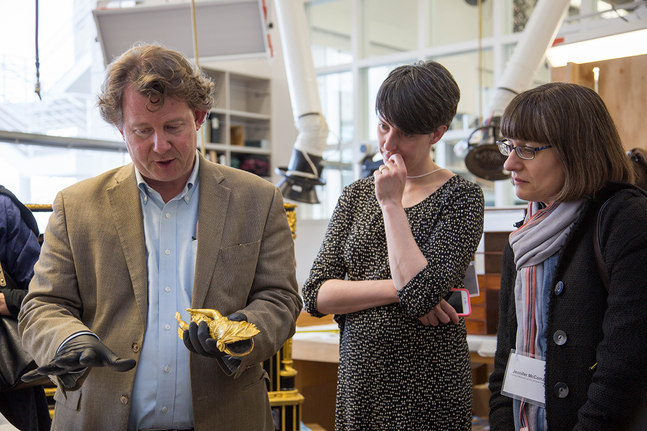 A museum conservator holds a small golden object in his hand, showing it to two women who look on intently