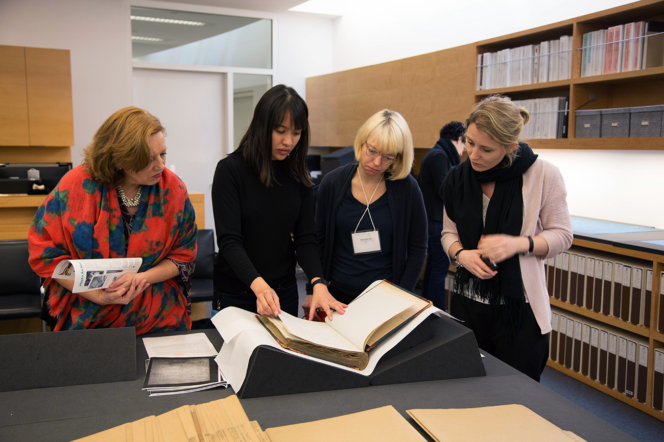 A group of four female scholars gather around a large book in a library setting, examining its contents