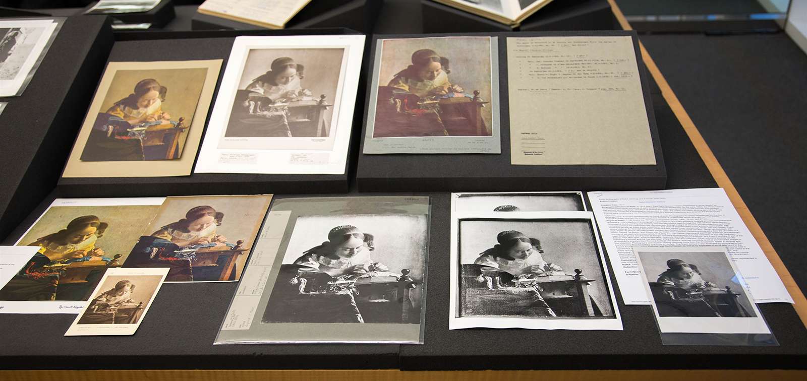 An array of reproductive photos and prints of a Vermeer painting are arrayed on a study table