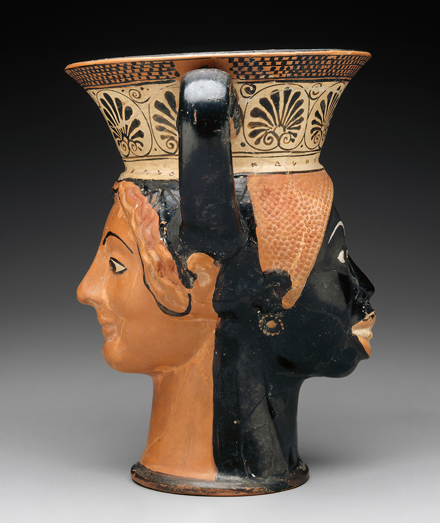 An ancient drinking cup in the form of two faces, side view, showing how one face is orange (Caucasian) and the other black (African)
