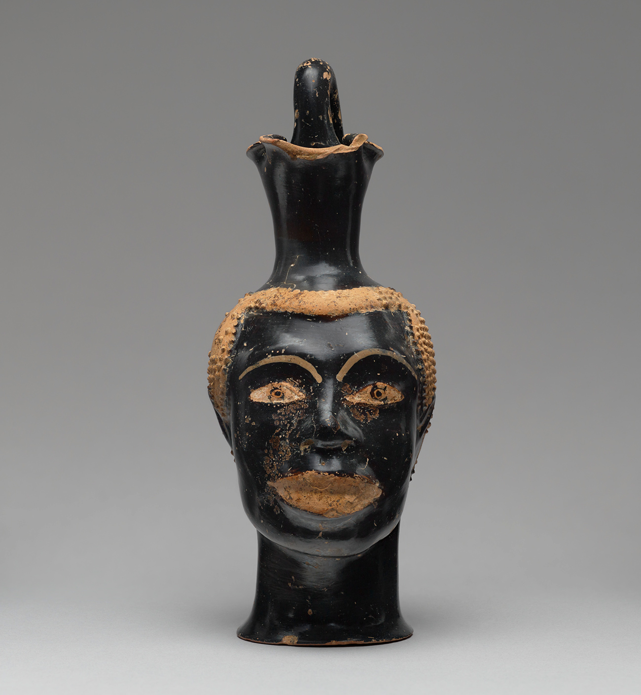 Front view of a black-painted ancient vase with large lips and clay-colored lips