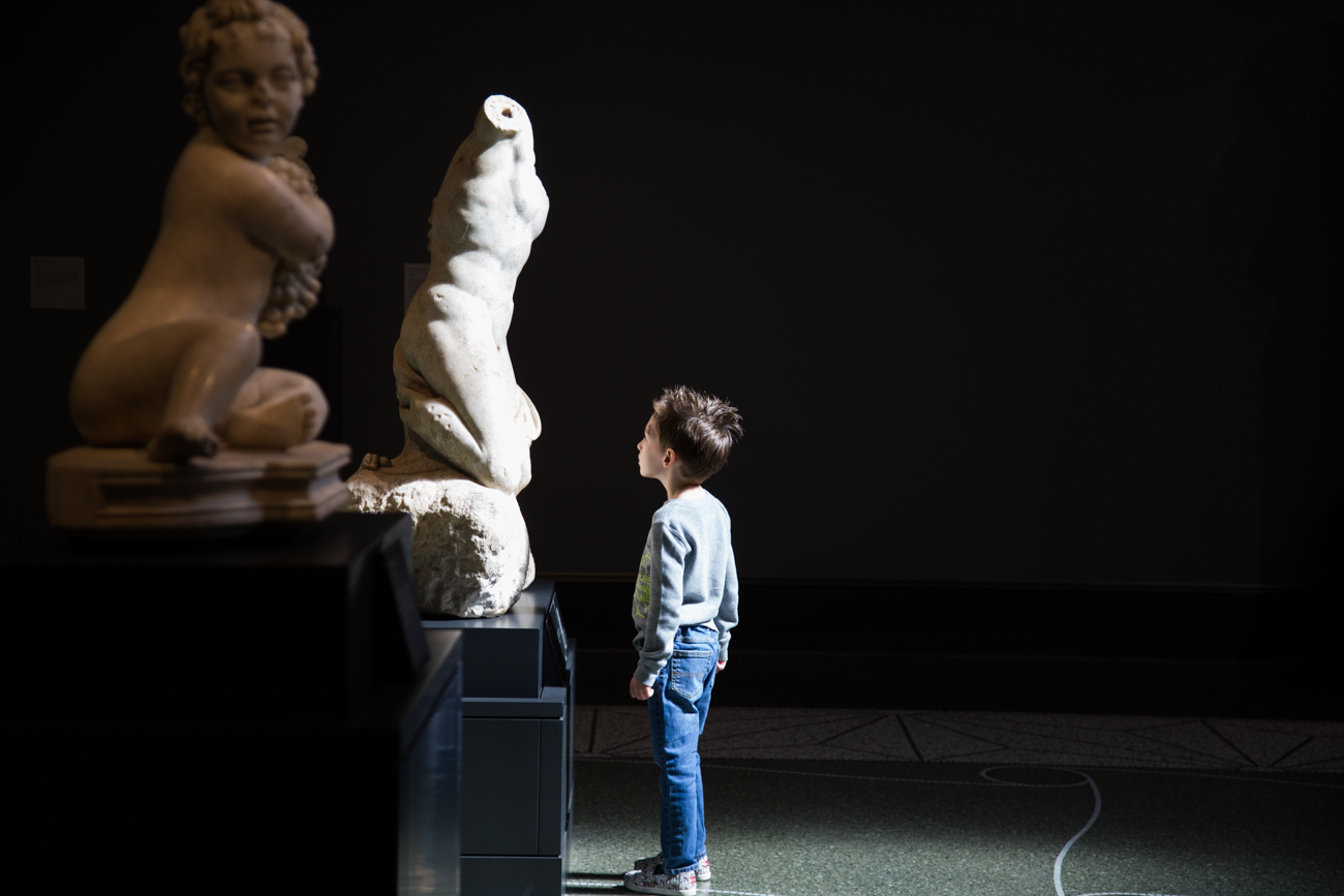 In a dark gallery of ancient sculptures, a young boy looks up at a marble torso in wonderment
