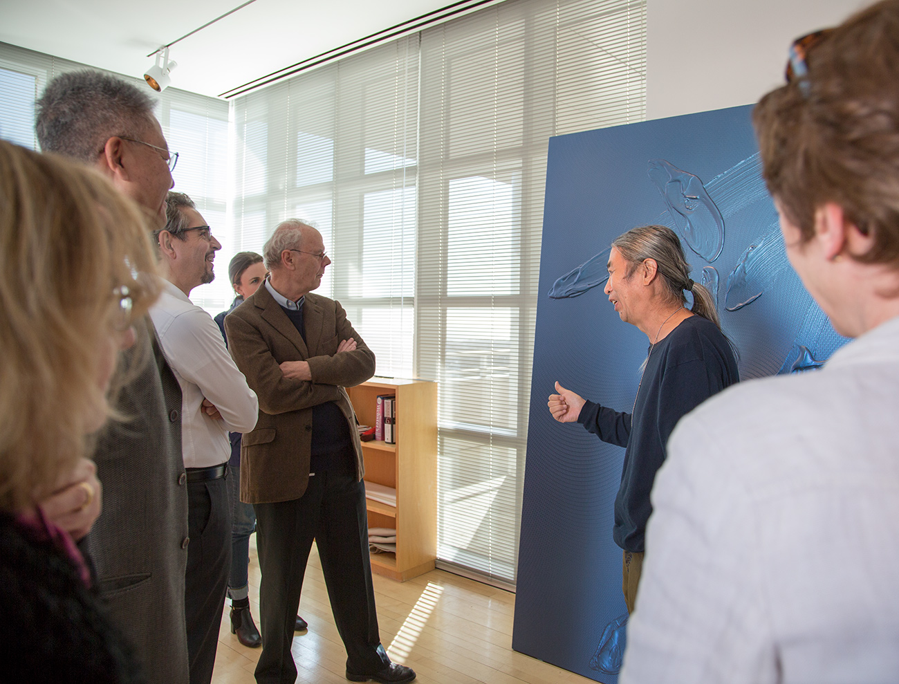 A small group gathers to admire a large blue painting on the floor, filled with gestural brushstrokes. At center, the artist speaks about his work
