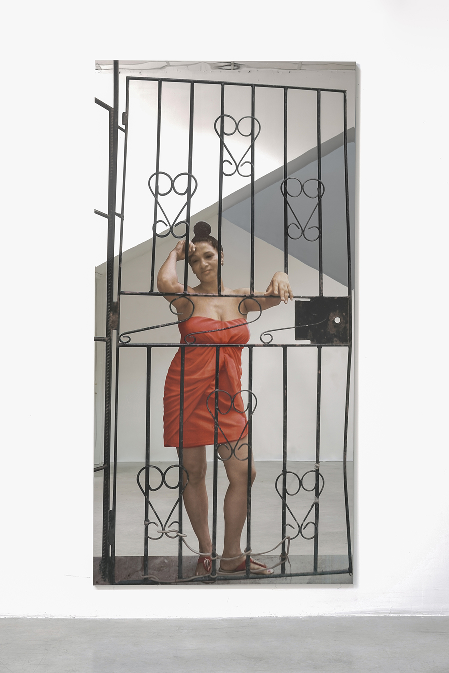 Against the background of a white room, a life-size young woman wearing a strapless red-orange dress faces forward, with her left arm and right elbow resting on the bars of a metal security door.