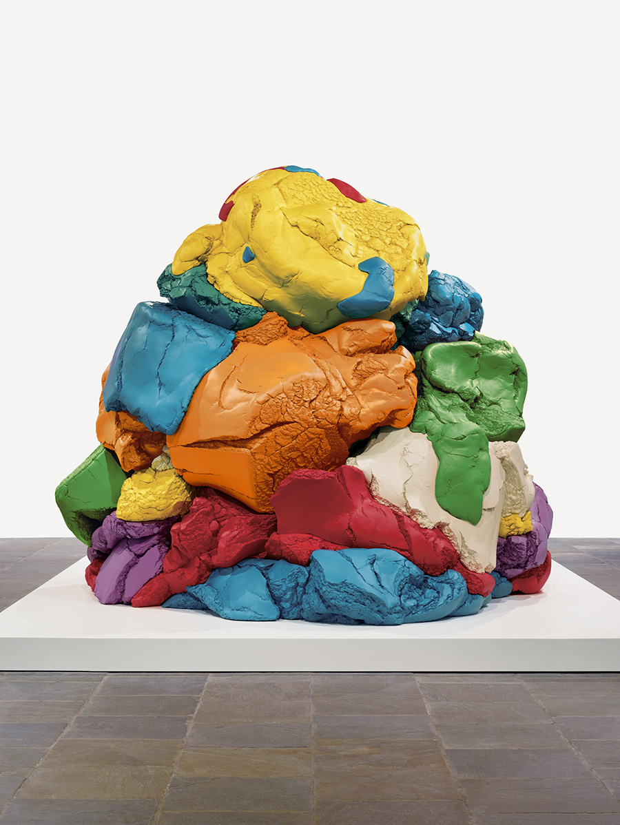 "Yellow, orange, fuschia, purple, green, marine blue, and white ""play-doh"" are mounded together in a slightly triangular pile."