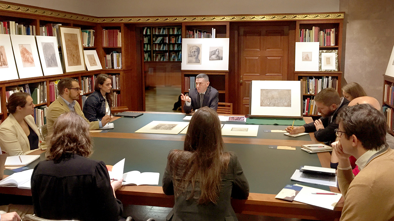 John Marciari speaks to graduate students sitting around a square table in a low-ceilinged room lined with bookshelves, as well as prints and drawings propped up on ledges.