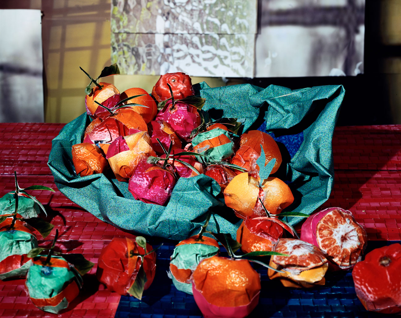 A photo illustration that appears to show a bowl of bright oranges, but on closer inspection, each object is made of crumpled and wrapped photos.