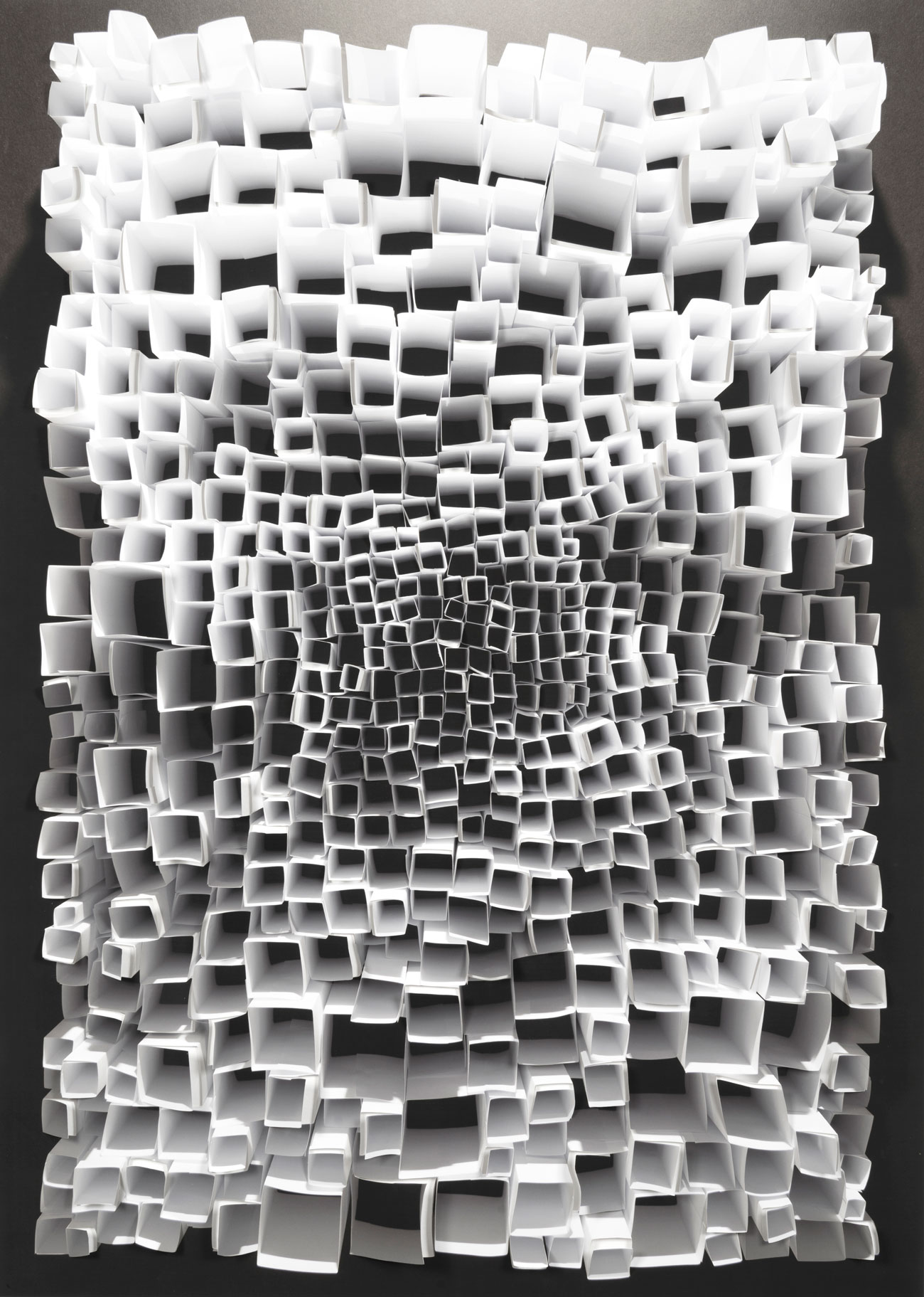 Black and white looking down upon an assembly of a paper folded into square tubes. The tubes of various sizes are arranged in a rectangle shape that fills the image.