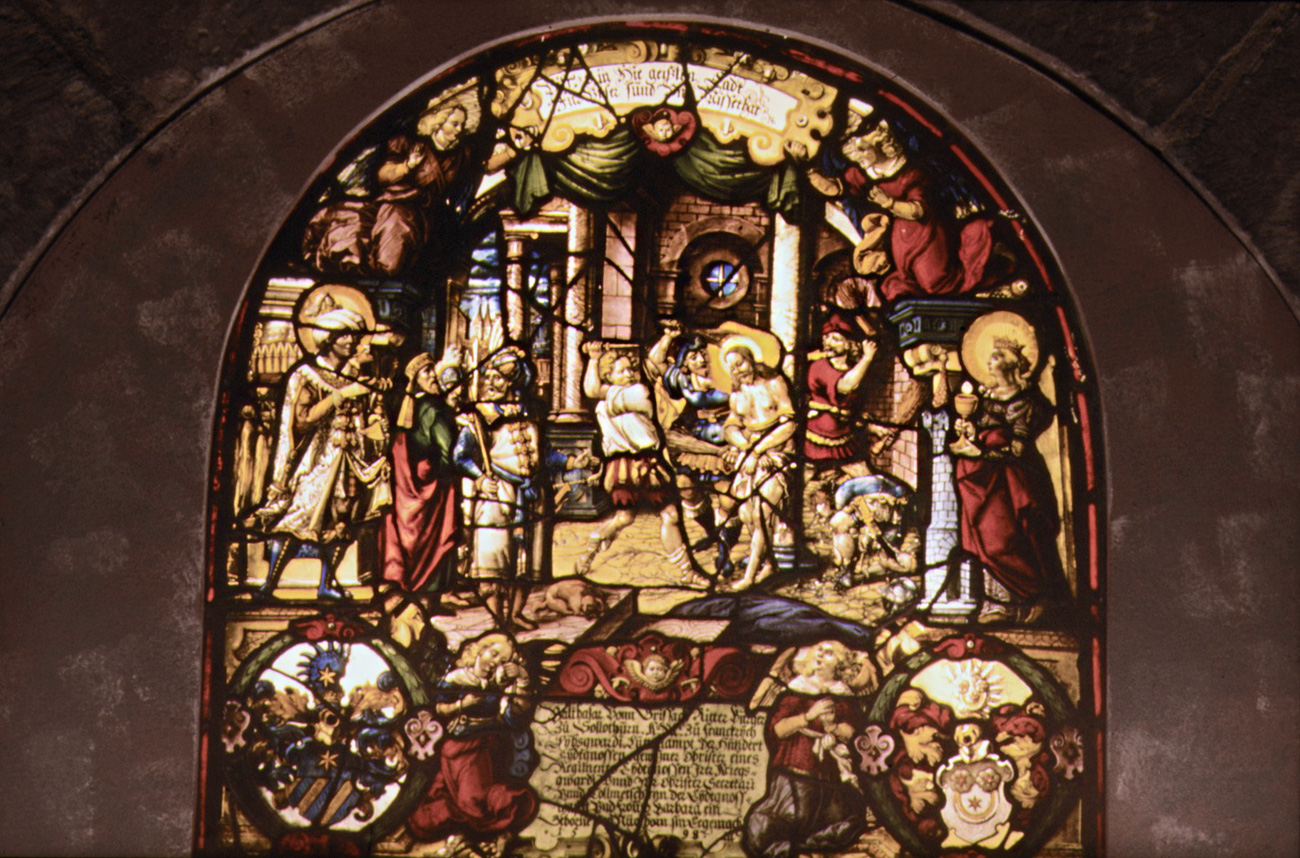 An intricate stained glass window showing Christ being beaten at center. Around him, text inscriptions and other scenes