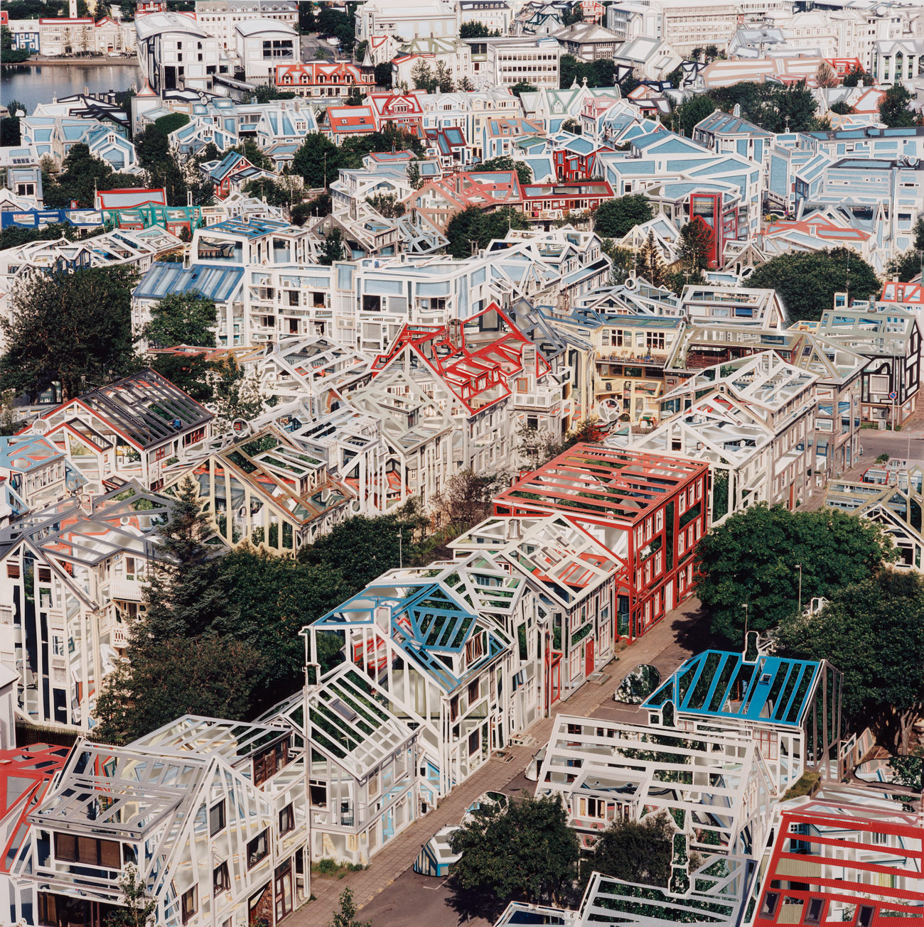 A photograph looking down upon a residential neighborhood in city has been altered to show transparent buildings with brightly colored frames.