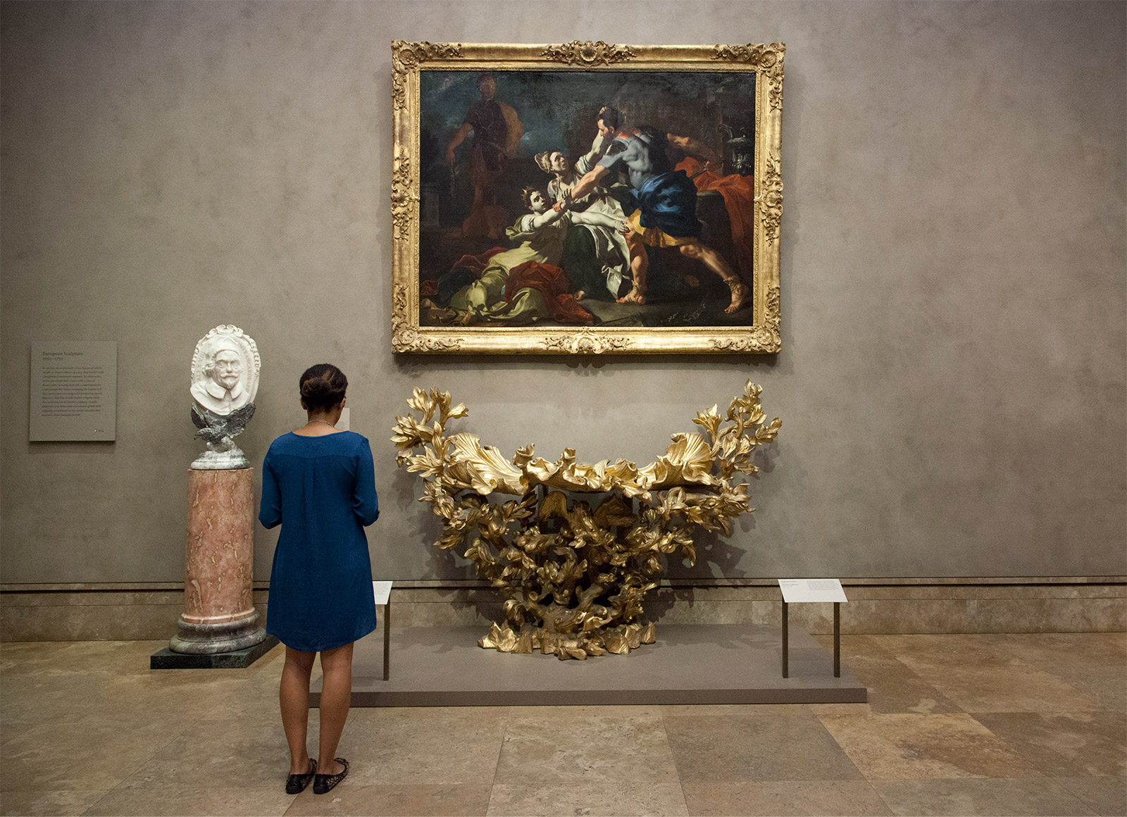 A woman stands in a gallery looking at a display consisting of a sculpture of a bust, a painting and a table composed of leafy gold branches.