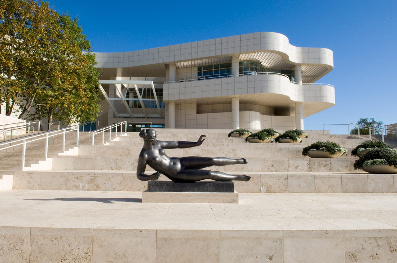 On the steps in front of a modern building, a larger than life metal sculpture of a woman appears on her side but with limbs raised as if floating.