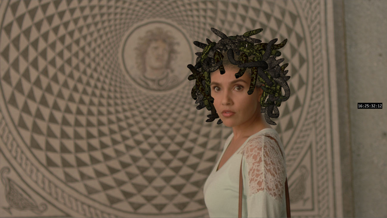 A woman stands in front of a mosaic of Medusa with a tangle of computer generated snakes on her head.