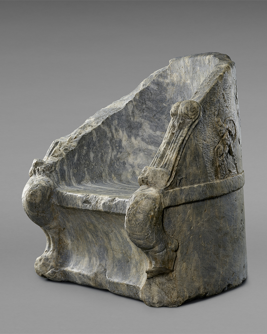 Made of gray and ivory-tinged marble, this hefty sculpted throne has a curved back and sloping arms that bear some fluted decorations. Slightly visible are decorations sculpted in low-relief that wrap around the back of the throne.