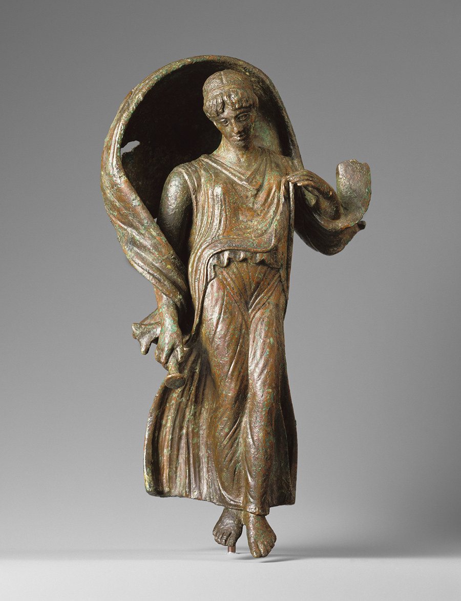 Made of green-tinged bronze, a woman with bare feet and a flowing dress takes a step forward as her wrap billows up behind her, framing her head.